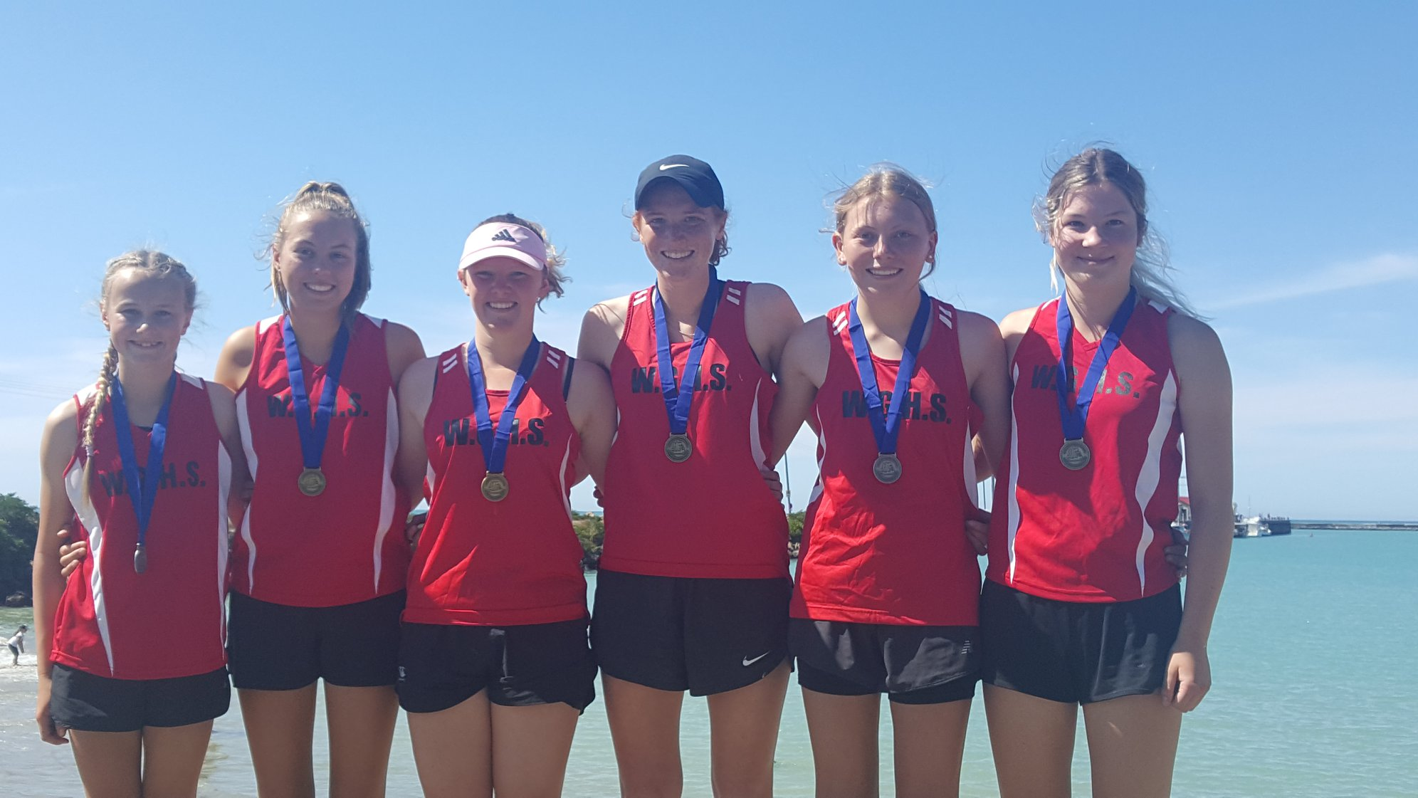Waitaki Girls High rowing team wearing medals with sea in the background